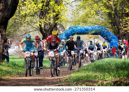 """ALMATY, KAZAKHSTAN - APRIL 19, 2015: Group of bikers started in action at cross-country competition """"Open season - Bikes relay 2015""""  - stock photo"""