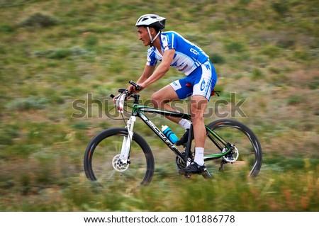 "ALMATY, KAZAKHSTAN - APRIL 29: J.Sankynaliev (N1) in action at Adventure mountain bike cross-country marathon in mountains ""Jeyran Trophy 2012"" April 29, 2012 in Almaty, Kazakhstan. - stock photo"