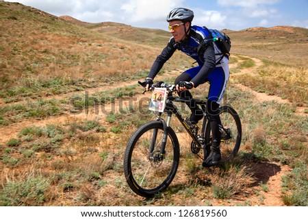 "ALMATY, KAZAKHSTAN - APRIL 30: M.Kolbasov (N14) in action at Adventure mountain bike cross-country marathon in mountains ""Jeyran Trophy 2011"" April 30, 2011 in Almaty, Kazakhstan. - stock photo"