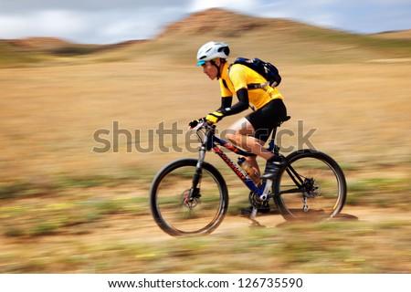 "ALMATY, KAZAKHSTAN - APRIL 30: N.Eleusizov (N12) in action at Adventure mountain bike cross-country marathon in mountains ""Jeyran Trophy 2011"" April 30, 2011 in Almaty, Kazakhstan. - stock photo"