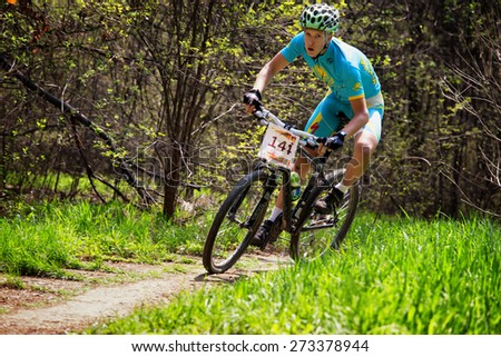 "ALMATY, KAZAKHSTAN - APRIL 19, 2015: N.Jurbin (N14) in action at cross-country competition ""Open season - Bikes relay 2015""  - stock photo"