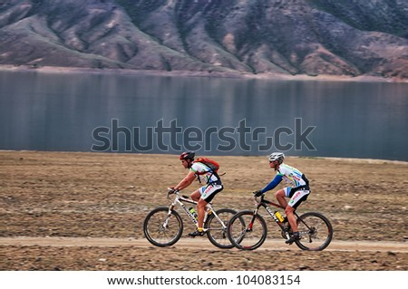 "ALMATY, KAZAKHSTAN - APRIL 29: S.Khazov (first) and K.Rachuk in action at Adventure mountain bike cross-country marathon in mountains ""Jeyran Trophy 2012"" April 29, 2012 in Almaty, Kazakhstan. - stock photo"