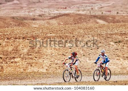 "ALMATY, KAZAKHSTAN - APRIL 29: S.Khazov (N27) and K.Rachuk(N25) in action at Adventure mountain bike cross-country marathon in mountains ""Jeyran Trophy 2012"" April 29, 2012 in Almaty, Kazakhstan. - stock photo"