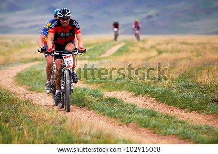 "ALMATY, KAZAKHSTAN - APRIL 29: T.Amirbekov (N13) in action at Adventure mountain bike cross-country marathon in mountains ""Jeyran Trophy 2012"" April 29, 2012 in Almaty, Kazakhstan. - stock photo"