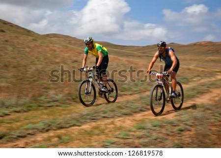 """ALMATY, KAZAKHSTAN - APRIL 30: T.Jurkashev (N37) and M.Sheynikov (N9) in action at Adventure mountain bike marathon in mountains """"Jeyran Trophy 2011"""" April 30, 2011 in Almaty, Kazakhstan. - stock photo"""