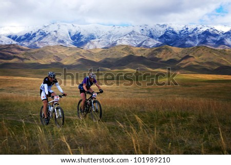 "ALMATY, KAZAKHSTAN - APRIL 30: V.Kachanov (N20) and K.Kelsinbekov (N22) in action at Adventure mountain bike marathon in mountains ""Jeyran Trophy 2012"" April 30, 2012 in Almaty, Kazakhstan. - stock photo"