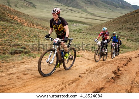 "ALMATY, KAZAKHSTAN - APRIL 30, 2016: V.Kachanov (N32) in action at Adventure mountain bike cross-country competition in mountains ""Jeyran Trophy 2016""  - stock photo"