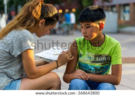 Almaty, Kazakhstan - July 27, 2014. Girl painting with henna on the hand of a boy. Center for pedestrians Almaty Zhibek Zholy Street (Silk Road). Here the center informals. - stock photo