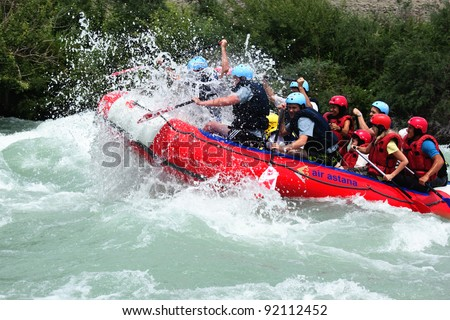 "ALMATY, KAZAKHSTAN - JUNE 27: ""Air Astana"" team in action at Rafting competition on Chilik river. June 27, 2011 in Almaty, Kazakhstan. - stock photo"