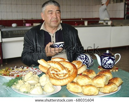 ALMATY, KAZAKHSTAN - JUNE 3: Man eating traditional foods on June 3, 2010 in Almaty, Kazakhstan. The national diet is heavy in carbohydrates and red meat in order to combat severe winter weather. - stock photo