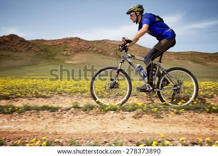 "ALMATY, KAZAKHSTAN - MAY 1, 2015: A.Ledyaev (N15) in action at Adventure mountain bike marathon ""Jeyran Trophy 2015"" - stock photo"