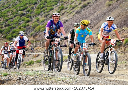 """ALMATY, KAZAKHSTAN - MAY 01: Competitors in action at Adventure mountain bike cross-country marathon in mountains """"Jeyran Trophy 2012"""" May 01, 2012 in Almaty, Kazakhstan. - stock photo"""