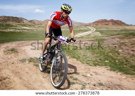 "ALMATY, KAZAKHSTAN - MAY 1, 2015: M.Balanenko (N18) in action at Adventure mountain bike marathon ""Jeyran Trophy 2015"" - stock photo"