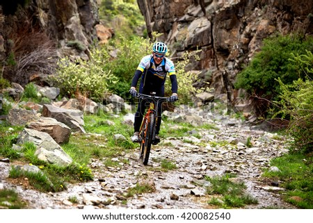"ALMATY, KAZAKHSTAN - MAY 01, 2016: Unknown rider in action at Adventure mountain bike cross-country competition in mountains ""Jeyran Trophy 2016""  - stock photo"