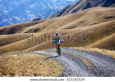 "ALMATY, KAZAKHSTAN - SEP 06, 2015: M.Sotnikov (N27) in action at Adventure mountain bike cross-country competition in mountains ""Bartogay Marathon 2015""  - stock photo"