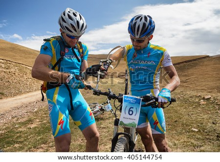 "ALMATY, KAZAKHSTAN - SEP 06, 2015: V.Vinokurov (left) repairs teammate (I.Makhmutov (N6) a broken prosthesis in action at Adventure mountain bike competition in mountains ""Bartogay Marathon 2015""  - stock photo"