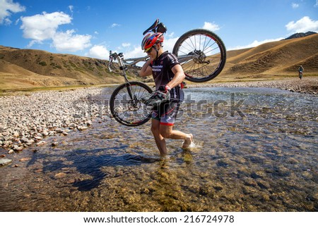 "ALMATY, KAZAKHSTAN - SEPTEMBER 09, 2014: I.Baranov (N26) in action at Adventure mountain bike cross-country marathon ""Marathon Bartogay-Assy-Batan 2014"". - stock photo"