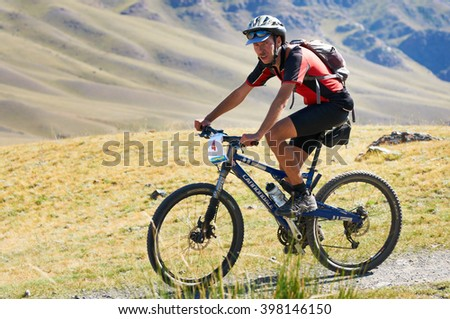 "ALMATY, KAZAKHSTAN - SEPTEMBER 04, 2011: P.Krasovetsky (N4)  in action at Adventure mountain bike cross-country marathon in mountains ""Marathon Bartogay-Assy-Batan 2011""  - stock photo"