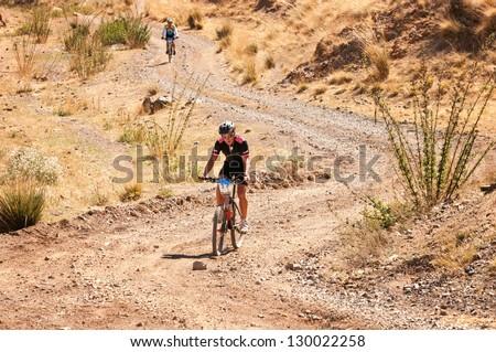 "ALMATY, KAZAKHSTAN - SEPTEMBER 09: R.Jukov (N17) in action at Adventure mountain bike cross-country marathon ""Marathon Bartogay-Assy-Batan 2012"" on September 09, 2012 in Almaty, Kazakhstan. - stock photo"