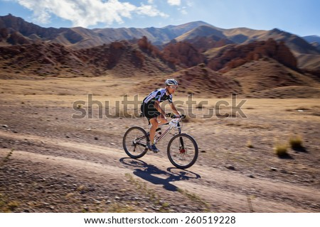 "ALMATY, KAZAKHSTAN - SEPTEMBER 09, 2014: V.Ganja (N3) in action at Adventure mountain bike marathon ""Marathon Bartogay-Batan"". Photo was taken with the effect of motion blur to show dynamics  - stock photo"