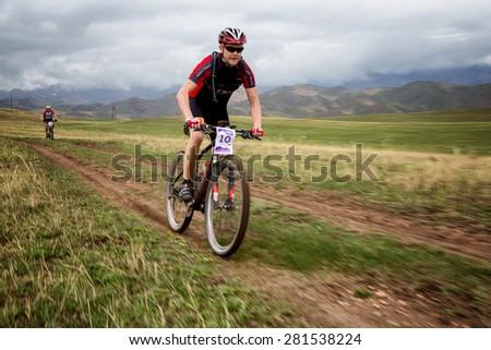 "ALMATY, KAZAKSTAN - MAY 02, 2015: A.Kovalgonov (N10) in action at Adventure mountain bike cross-country marathon in mountains ""Jeyran Trophy 2015""  - stock photo"