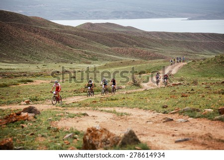"ALMATY, KAZAKSTAN - MAY 02, 2015: Competitors in action at Adventure mountain bike cross-country marathon in mountains ""Jeyran Trophy 2015""  - stock photo"