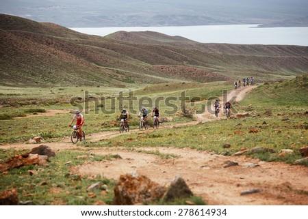 "ALMATY, KAZAKSTAN - MAY 02, 2015: Competitors in action at Adventure mountain bike cross-country marathon in mountains ""Jeyran Trophy 2015""  - stock photo"