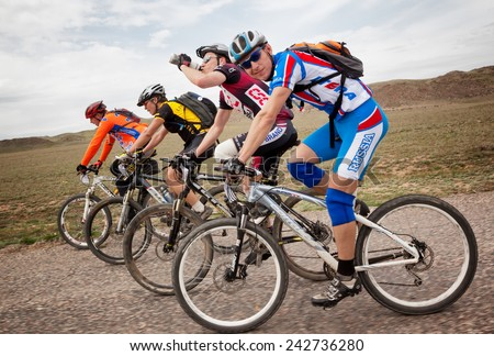 "ALMATY, KAZAKSTAN - MAY 01, 2010: Group of unknown riders in action at Adventure mountain bike cross-country competition in mountains ""Jeyran Trophy 2010""  - stock photo"