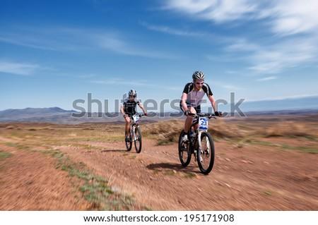 "ALMATY, KAZAKSTAN - MAY 01, 2014: I.Shishkin (N23) in action at Adventure mountain bike cross-country marathon in mountains ""Jeyran Trophy 2014""  - stock photo"