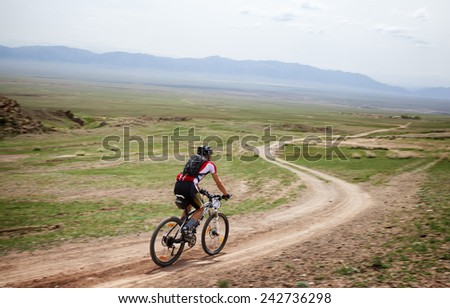 "ALMATY, KAZAKSTAN - MAY 01, 2010: Unknown rider in action at Adventure mountain bike cross-country competition in mountains ""Jeyran Trophy 2010""  - stock photo"
