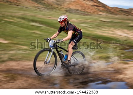 "ALMATY, KAZAKSTAN - MAY 01, 2014: V.Kachanov (N17) in action at Adventure mountain bike cross-country marathon in mountains ""Jeyran Trophy 2014""  - stock photo"