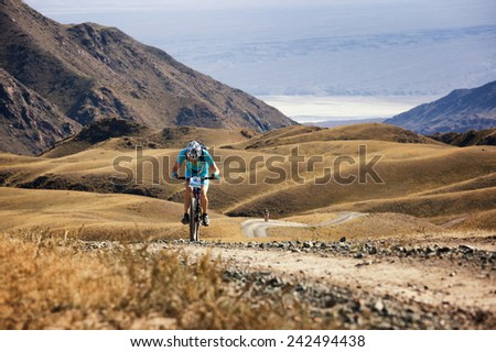 "ALMATY, KAZAKSTAN - SEP 09, 2009: N.Eleusizov (N3) in action at Adventure mountain bike cross-country competition in mountains ""Bartogay marathon 2009""  - stock photo"
