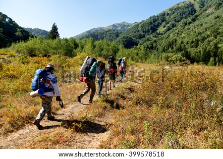 ALMATY REGION, KAZAKHSTAN - AUGUST 07, 2014: People hike to the Zhasylkol lake in Dzungarian Alatau mountains.