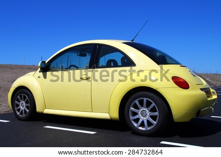 Almere, Flevoland, The Netherlands - June 6, 2015: Yellow Volkswagen Beetle parked on a public parking lot - stock photo