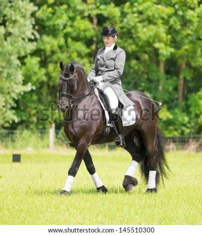 ALMERE - JULY 7: Equestrian Esther Liano demonstrates her horse-riding skills in upper-level dressage during the annual Horse & Outdoor horse show, July 7, 2013 in Almere, The Netherlands - stock photo