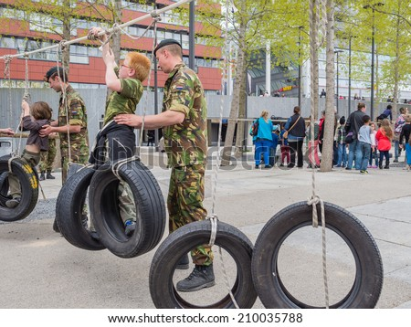 ALMERE, NETHERLANDS - 23 APRIL 2014: Children battling part of a military assault course on National Army Day meant to make the public acquainted with the army - stock photo