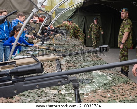 ALMERE, NETHERLANDS - 23 APRIL 2014: On National Army Day kids of all ages  are allowed to hold machine guns of all sorts under guidance of the military in Almere - stock photo