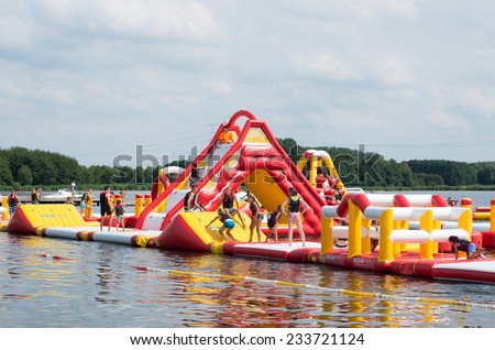 ALMERE, NETHERLANDS - AUGUST 3, 2014: Unknown people on an inflatable obstacle course in a lake. Almere is the youngest and fastest growing city in the country, founded around 1975. - stock photo