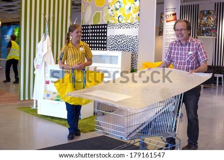ALMHULT, SWEDEN-FEBRUARY 19, 2012: IKEA welcome girl employee and man with a shopping trolley after shopping at the Ikea store of Almhult, the founder Ingvar Kamprad's hometown.