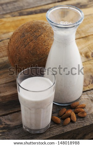 Almond and coconut milk. Healthy blended almond and coconut on wooden table. Studio shot at daylight, shallow depth of field. - stock photo