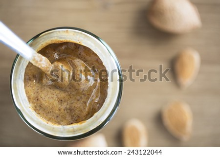 Almond Butter in jar with spoon, from directly above - stock photo