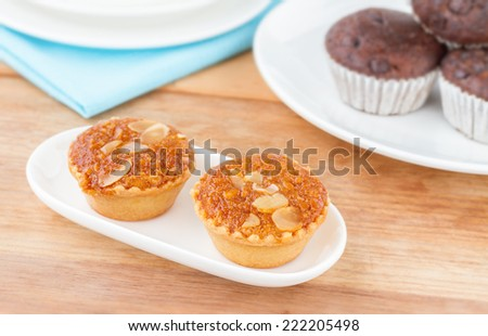 Almond Cakes, Almond with Banana Cake, Fresh Almond Bakery Cake, Banana Cake Topped with Almonds or Almond banana bread on white plate wooden table, Sweet and Snack for tea time  - stock photo