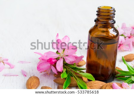 Almond essential oil, flowers and nuts.