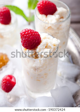 Almond milk and orange zest granita with fresh raspberries in glasses on a vintage metal tray with ice cubes and mint leaves - stock photo