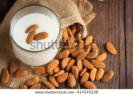 Almond milk in a glass with almond nuts on a wooden table. Healthy food and drink concept. - stock photo
