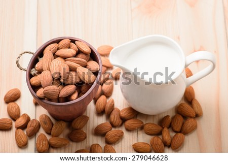 Almond milk in a jar with almond on a wooden table - stock photo