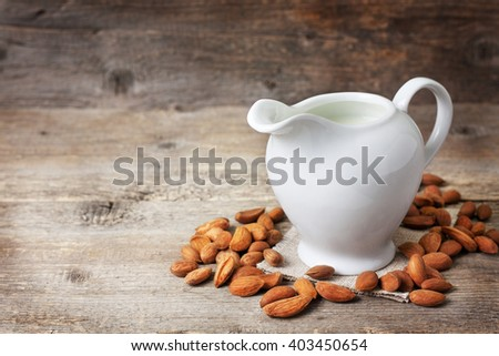 almond milk in the jug of milk ,  almond on the old wooden background - stock photo
