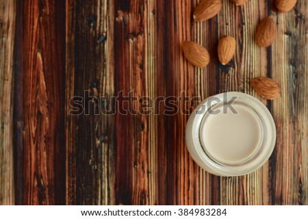 Almond milk with almond nuts on a wooden table  - stock photo