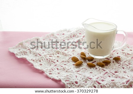 Almond milk with almond on a  pink table lactose free  - stock photo