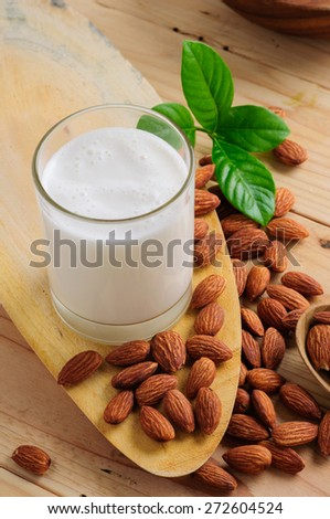 Almond milk with almond on a wooden table - stock photo